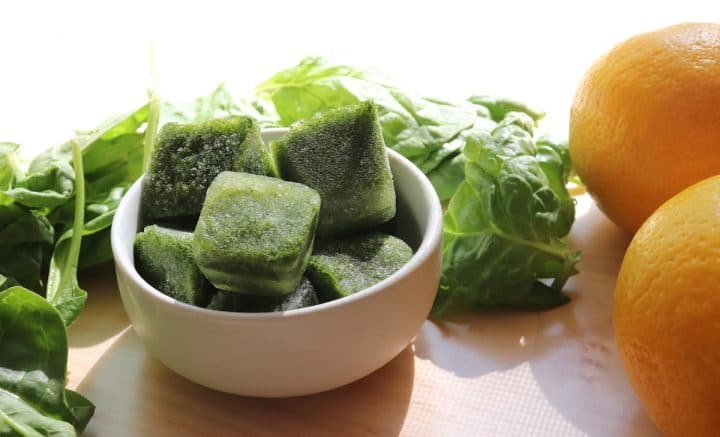 Bowl of frozen spinach cubes to use in a smoothie.