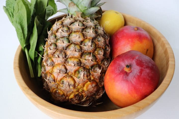 Wooden bowl filled with spinach, pineapple, mangos and a lemon.
