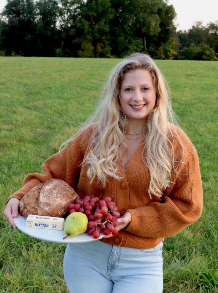 Olivia Sokolowska, creator of Salted Butter Kitchen, holding a marble tray filled with bread, butter, and fruit.